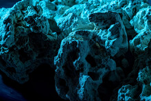 A Pile Of Stones Forming A Cave, Illuminated By An Ominous Blue Light. Selective Focus. Background, Backstage, Template For Your Creativity.