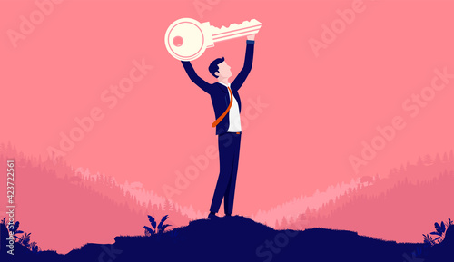 Photo Key to success - Man holding key over head, metaphor for having a successful career