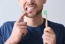 Man With Aching Teeth And Brush On Grey Background