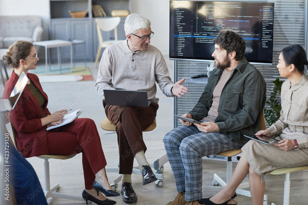 Fototapeta High angle view at contemporary diverse business team sitting in circle during strategy meeting, focus on senior businessman in center
