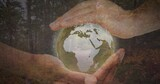Composition of man holding globe with forest in background