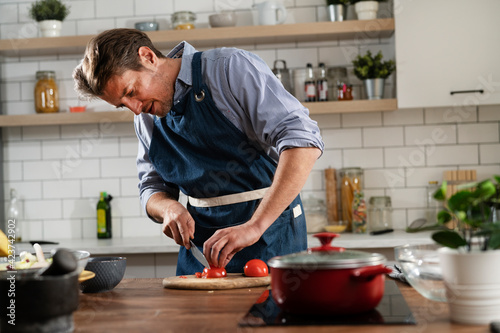Fototapeta Young man preparing vegetable salad in the kitchen
