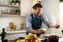 Happy Man Preparing Food At Home. Chef Cooking Tasty Meal In Kitchen.
