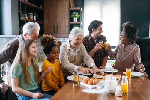 Fototapeta Multi ethnic and generational family cooking in kitchen together obraz