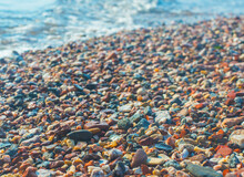 Bright Wet Pebbles On The Coast In The Foam Of The Surf