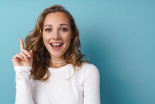 Blonde Happy Woman Pointing Finger Upward And Smiling