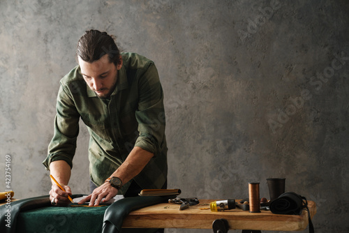 Obraz Bearded focused craftsman working with leather while standing at table - fototapety do salonu