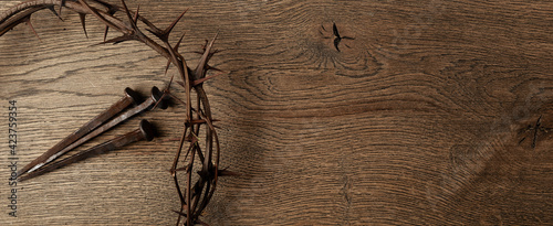 Slika na platnu Crown of thorns with three nails on wooden background