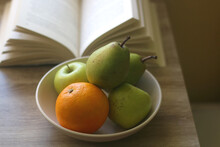 Bowl With Pears, Appples And Oranges And Open Book On A Table. Selective Focus.