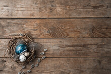 Nest With Easter Eggs, Feathers And Pussy Willow Twigs On A Wooden Background. Space For Text