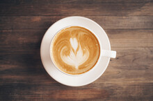 Cup Of Coffee With Latte Art On Wooden Background