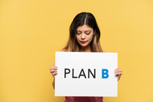 Young Russian Girl Isolated On Yellow Background Holding A Placard With The Message PLAN B With Sad Expression