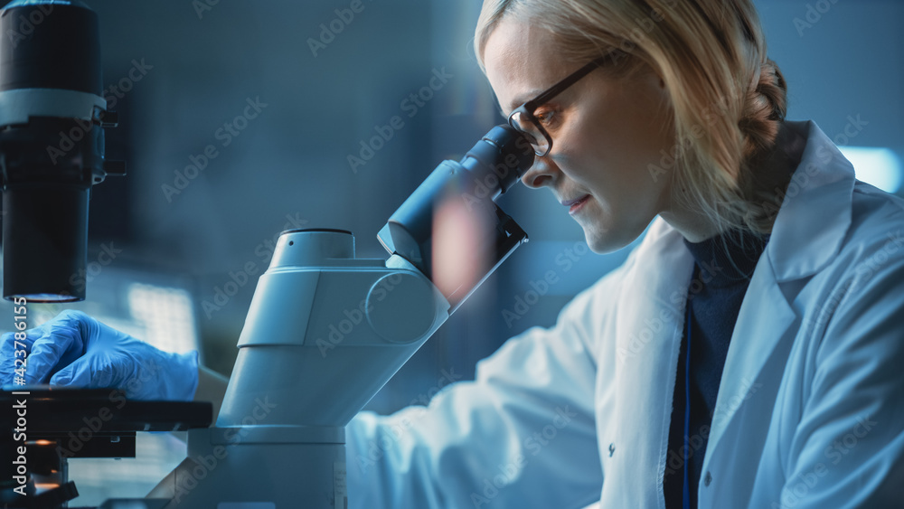 Fototapeta Close Up Portrait of a Medical Research Scientist Conducting DNA Experiments Under a Microscope in a Biological Applied Science Laboratory. Beautiful Female Lab Engineer in White Coat.