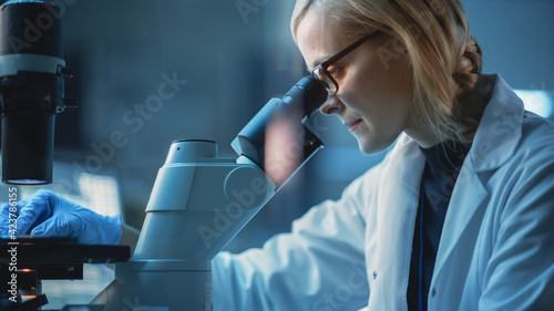 Close Up Portrait of a Medical Research Scientist Conducting DNA Experiments Under a Microscope in a Biological Applied Science Laboratory. Beautiful Female Lab Engineer in White Coat.