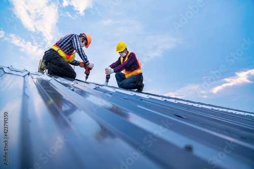 Billede på lærred Tow construction worker safety wear using electric drill tools install on new roof metal sheet, Roof construction concept