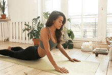 Self-determined Flexible Young Hispanic Female In Crop Top And Leggings Training Indoors, Doing Cobra Pose, Opening Chest, Improving Mobility Of Spine. Slim Fit Girl Stretching Body On Yoga Mat