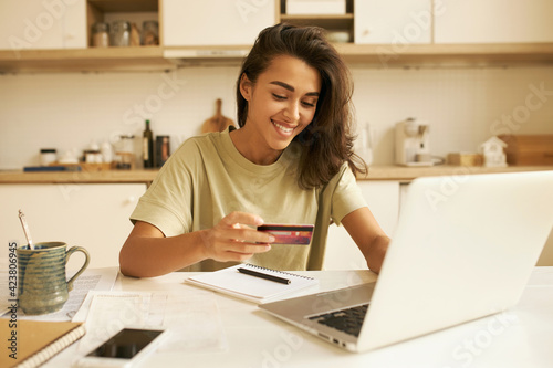 Stylish pretty student girl surfing internet in kitchen, sitting at table with open laptop and mug, holding plastic credit card, entering information via paying system while shopping online