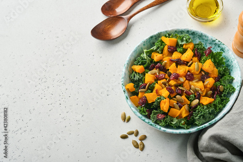 Fototapeta Fall salad with kale, roasted pumpkin, seeds and dried cranberries in bowl