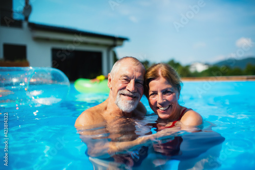 Obraz Cheerful senior couple in swimming pool outdoors in backyard, looking at camera. - fototapety do salonu