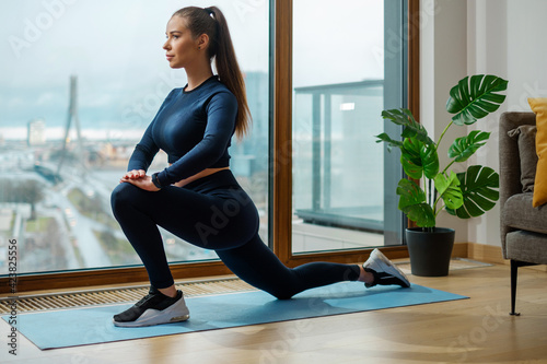 Obraz Woman in tracksuit does exercise in warrior pose on mat - fototapety do salonu