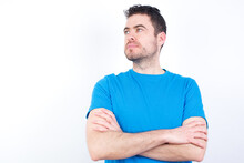 Charming Thoughtful Young Handsome Caucasian Man Wearing White T-shirt Against White Background Stands With Arms Folded Concentrated Somewhere With Pensive Expression Thinks What To Do