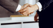 Unknown businessman shaking hands with his colleague or partner while standing straight in modern office, close-up. Business people group at meeting