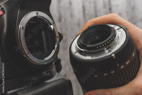 the photographer attaches the lens to the SLR camera Fototapete