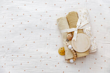 Newborn Background. Baby Muslin With A Bow And Bib. Empty Wooden Card. Gift For A Newborn Baby