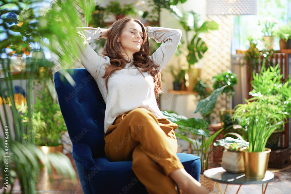 Fototapeta relaxed woman with long wavy hair at home in sunny day