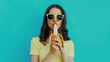 Portrait of young woman eating banana on a blue background