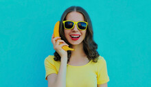 Portrait Of Funny Woman Calling On A Banana Phone On A Blue Background