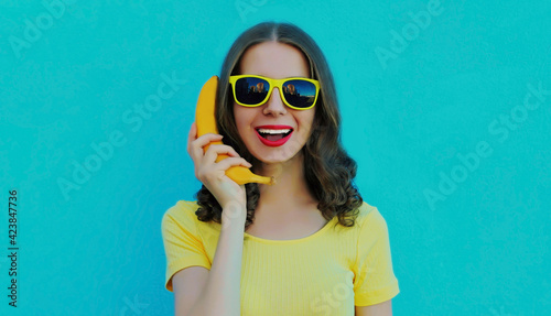 Fotografia Portrait of funny woman calling on a banana phone on a blue background