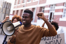 African American Man Using Megaphone With Protesters On March Holding Signs And Raising Fists