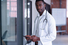 Portrait Of African American Male Doctor Wearing White Coat And Stethoscope Using Digital Tablet