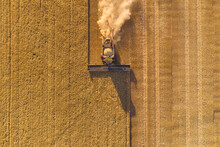Aerial View Looking Down On A Header Harvesting A Barley Crop In The Late Afternoon