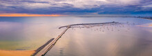 Aerial View Of A Jetty And Breakwater On A Calm Bay At Sunset