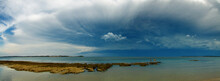 Panoramic View Of A Large Stormfront Developing Over A Rocky Coastline As Three Beachgoers Look On