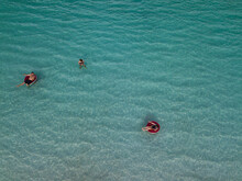 Family Swimming In Clear Blue Water