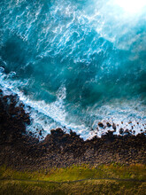 Aerial Perspective - Green Grass, A Dirt Trail, And Crashing Blue Waves