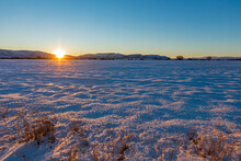USA, Idaho, Bellevue, Sun Setting Over Snowy Field