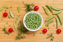 Fresh Green Peas In White Bowl, Red Tomatoes, Dill And Pear Pods On Wooden Background. Raw Organic Food Mix. Fresh, Healthy, Vegan Food Concept. Flat Lay Photo.