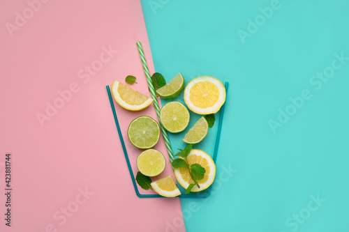 A glass made of lime and lemins on colorful background. Fototapet