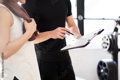 Obraz トレーニングのアドバイスをするアジア人男性パーソナルトレーナー - fototapety do salonu