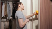 Dark Haired Woman With Bun Hairstyle Cleans Large Mirror On Door Of Wooden Wardrobe, With Soft Orange Rag In Brightly Lit Walk-in Closet At Home