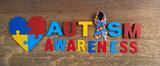 Fototapeta Kawa jest smaczna - Autism awareness. Autism awareness ribbon, heart and word autism on wooden background background.