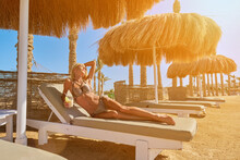 Sexy Woman Wearing Bikini Sitting On Lounger Under Straw Canopy Umbrella At The Beach Holding Glass With Cocktail Or Drink