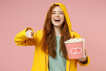 Redhead Young Woman In Yellow Waterproof Hood Raincoat Outerwear Hold Pop Corn Takeaway Bucket Point Finger Camera On You Isolated On Pastel Pink Background Studio. Lifestyle Fall Season Concept