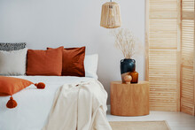 Dark Orange And Grey Pillow On King Size Bed, Copy Space On Empty Wall