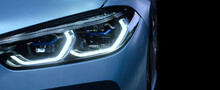 Close-up Front Headlight With Xenon Light Of Blue Modern Car On Black Color Background And Copy Space