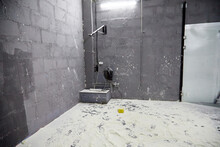 A Room With Brick Walls And White Powder, Whitewash, Or Flour On The Floor. Photo Studio For Photography With Flour